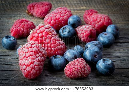 Fresh Raspberries And Blueberries On Wooden Table