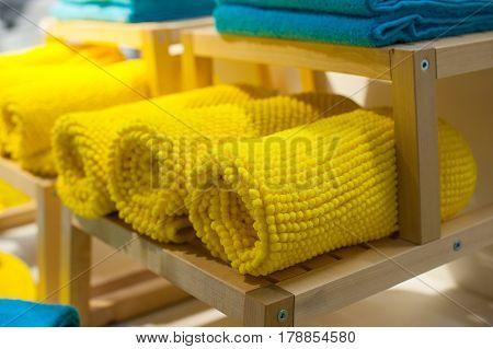 yellow towels on the shelf in the closet.