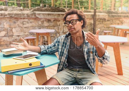 Handsome african young man sitting and talking in outdoor cafe