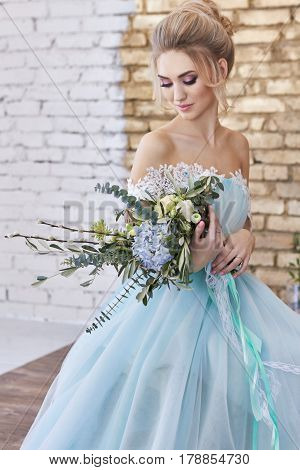 Bride in a beautiful turquoise dress in anticipation of wedding. Blonde in lace dress sea green with a bouquet . Happy bride emotion joy on her face. Beautiful makeup manicures and hairstyles women