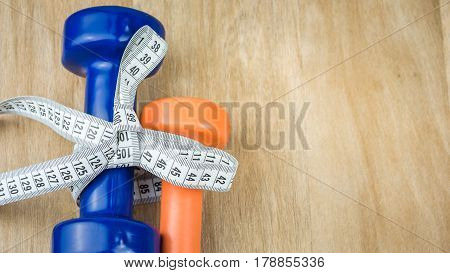 Blue and orange dumbbells bound together with centimetric tape as gift on wooden background.
