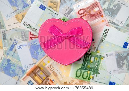 Gift box in the form of heart on a background of Euro currency