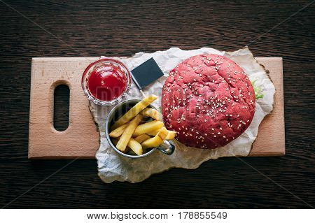 Red burger on a wooden board with fries and sauce