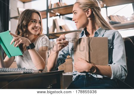 smiling women students having conversation while studying together
