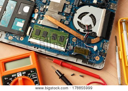 Disassembled laptop and equipment for computer repairing.