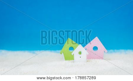 Symbol of tree coloured little houses on the sand on bright blue background.