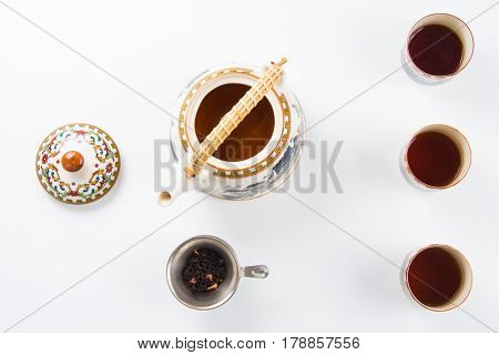 High angle view of a set of tea pot, tea leaves and strainer on a white background