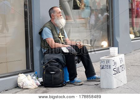 Oslo Norway - July 22 2014: homeless man on the main street Karl Johans Gate in front of a clothing boutique. This street is one of the busiest of the city full of shops bars hotels and terraces.