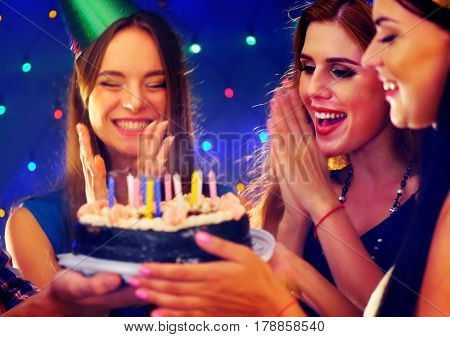 Happy friends birthday party with candle celebration cakes. Girl joyfully clapping. Small group people looking at burning candles in night spot. Women have fun hen-party on dark background.