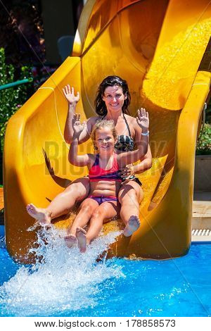 Swimming pool slides for family with children on water slide at aquapark . Kid with mother holiday outdoor. Girl and woman hands up in aqua park. Flowing water with people in summer water park .