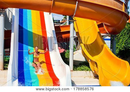Swimming pool slides for children on water slide at aquapark . Summer kid holiday outdoor. Happy little girl with super gesture in aqua park.