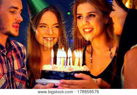 Happy friends birthday celebrating food with celebration cakes. Meet group people wear in hat holding cake with candles at burning candles. Women and men have fun and flirting in nightclub.