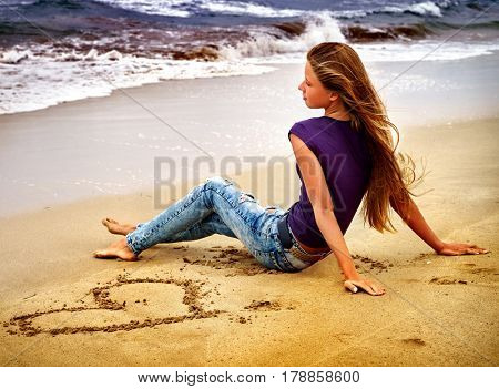 Woman on beach in sunset writing on sand. Teenager girl write heart on sea shore. Hipster in ripped hole jeans summer style outfit sitting near ocean.