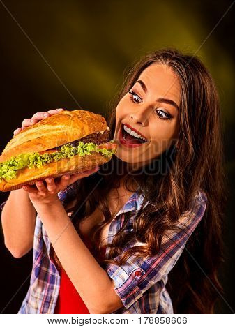 Woman eating hamburger. Student consume fast food. Girl bite of very big burger . Girl trying to eat a lot of junk. Advertise fast food on black background.