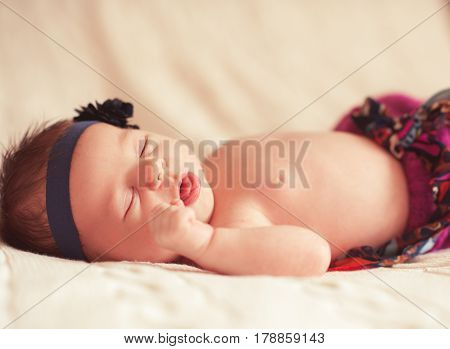 Cute baby girl sleeping in bed closeup. Newborn child lying on beige cover. Bedtime.