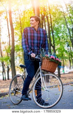 Man on bicycle with flowers basket is riding summer park outdoor in sunlight.