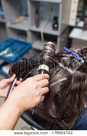 Styling female hair dryer in the beauty salon