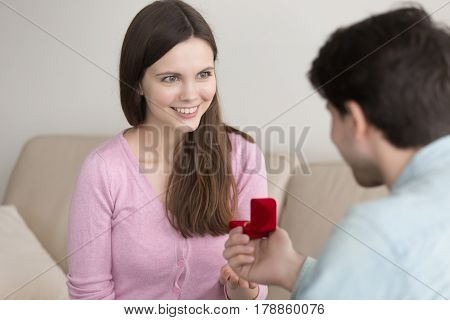 Young handsome guy holding red box with engagement ring, making marriage proposal to girlfriend, requesting a hand, indoors. Romantic concept, asking to marry, birthday gift, wedding planning