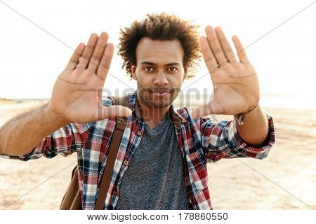 Handsome african man standing and focusing with his hands outdoors