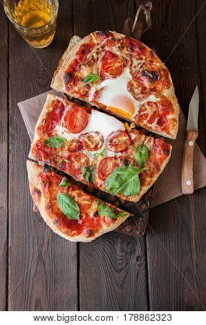 Top View Of Pizza With Tomato Sauce Egg And Basil On A Wooden Board Knife Galss Of Beer. Copy Space.