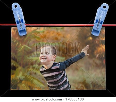 photo boy on a rope with clothespin on a black background .