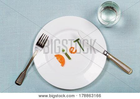 White plate with word diet made of colorful pieces of vegetables and glass of pure on blue teblecloth background. Flat lay. Top view. Concept of healthy eating and raw food dieting.