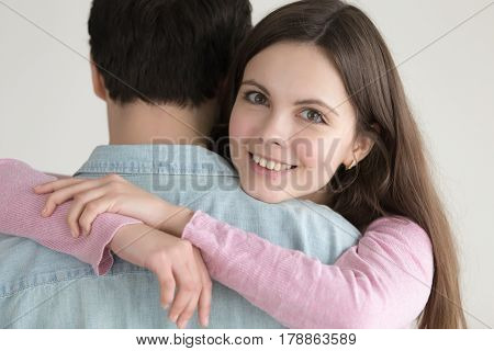 Young lady looking at camera and smiling, hugging her boyfriend, loving woman embracing guy holding tight, affectionate couple, absolutely happy wife showing love to husband