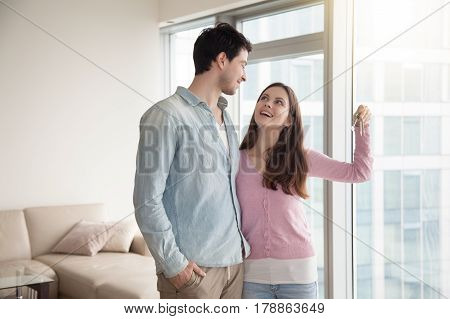 Young smiling couple holding and showing keys of their new own home, happy family buying or renting house or apartment, paid real estate mortgage, teenagers left parental home, starting married life