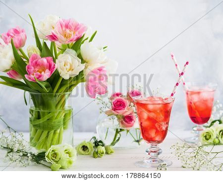 Refreshing summer drink with strawberry in  glasses and flowers in vase on wooden table