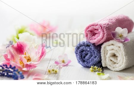 Towels different colors and fresh flowers  on white wooden background