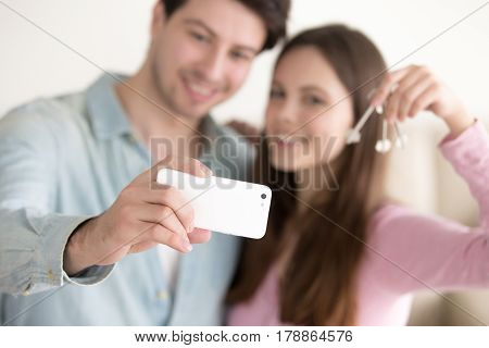 Happy smiling young couple showing keys of their new home and taking selfie picture to remember starting new life in own apartment, satisfied glad house owners with keys making photo on mobile phone
