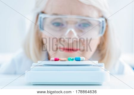 Portrait Of Senior Woman Scientist Looking At Pills On Lab Scales