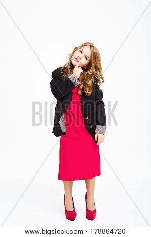 Charming little girl in mother's outfit looking away dreamily with pointer finger on chin.