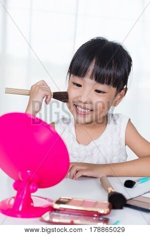 Asian Chinese little girl applying makeup with cosmetics in the dressing room for makeover.