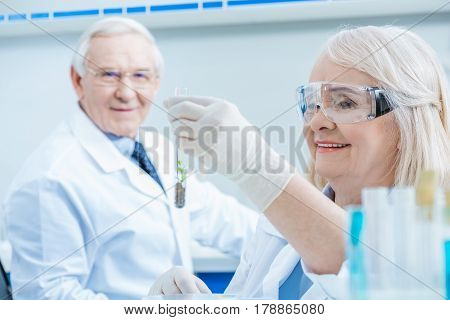 Man Scientist Looking At Smiling Colleague Holding Green Plant In Test Tube
