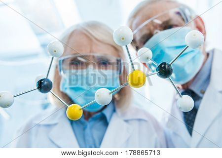 Chemists In Protective Workwear Looking At Molecular Model