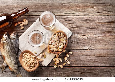 Lager beer glasses and snacks on wooden table. Nuts, chips, dry fish. Top view with copyspace