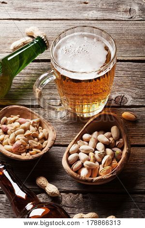Lager beer mug, bottles and snacks on wooden table. Various nuts