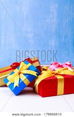 Gift boxes with bow. Colored presents wrapped with paper and ribbons. Christmas or birthday packages. Celebration design. Blue background.