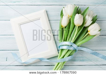 White tulips bouquet and blank photo frame on wooden background. With space for your greetings