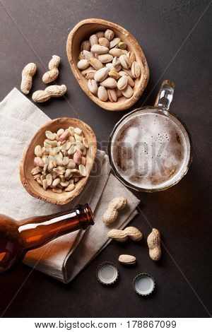 Lager beer mug, bottle and snacks on stone table. Various nuts. Top view