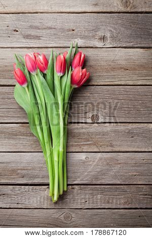 Red tulips bouquet on wooden background. Top view with space for your text