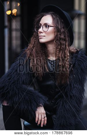 Portrait of a beautiful girl with brown eyes in glasses in a black hat and coat with fur in the cityscape looking away. The girl is like Harry Potter.