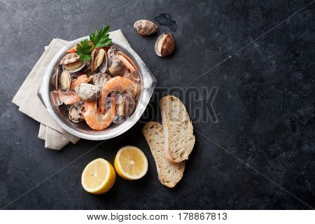 Fresh seafood on stone table. Scallops and shrimps. Top view with copy space