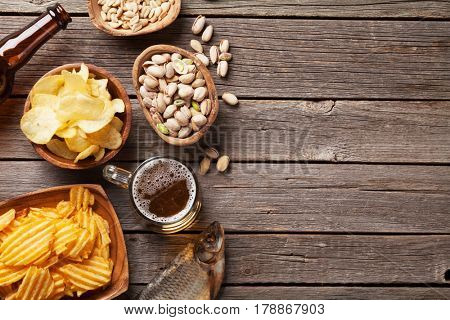 Lager beer mug and snacks on wooden table. Nuts, chips, dry fish. Top view with copy space