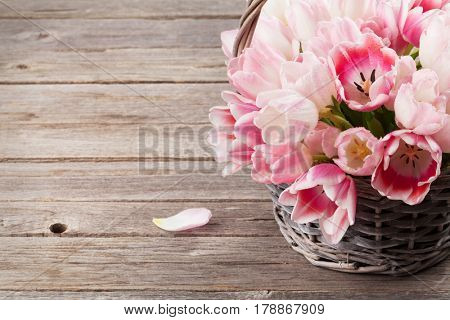 Pink tulips bouquet basket on wooden table. With space for your greetings