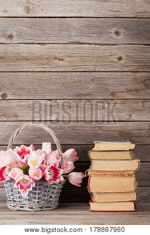 Pink tulips bouquet basket and old books in front of wooden wall with copy space