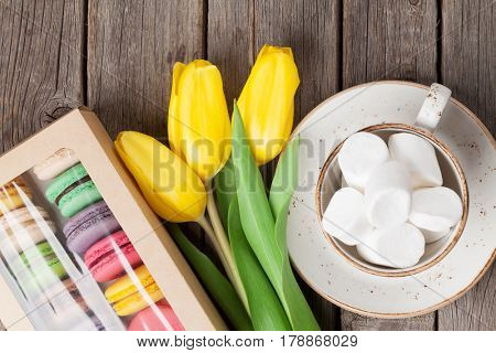 Colorful macaroon cookies and yellow tulips bouquet on wooden table. Top view