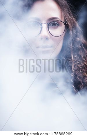 Portrait of a beautiful girl with brown eyes in glasses in a cloud of smoke looking in camera. The girl is like Harry Potter.