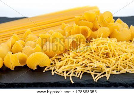 Three types of pasta on dark shale plate on white background